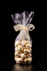 Chocolate mini eggs in a cellophane bag, black background