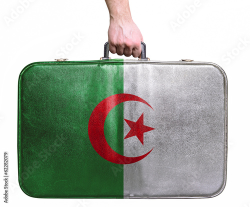 Tourist hand holding vintage leather travel bag with flag of Alg