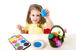 little girl painting dyed egg for Easter celebration