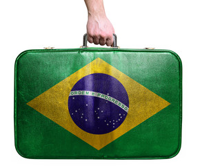Tourist hand holding vintage leather travel bag with flag of Bra