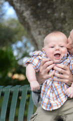 mother kissing smiling baby boy