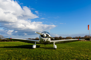 White propeller plane on a grass airfield with blue sky