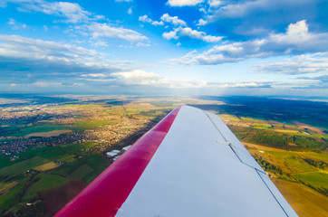 Aerial view of a plane wing flying over green fields