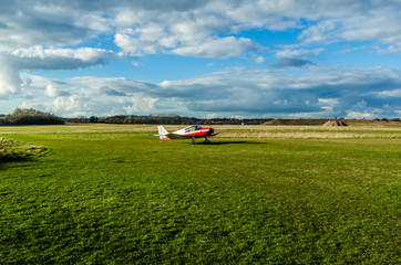 Red plane on a grass airfield preparing to take off