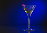 wineglass with martini and olives on blue background.