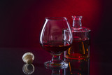 Cognac bottle and glass on the red background.