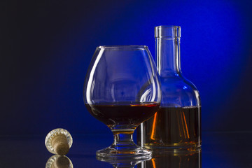 Cognac bottle and glass on the blue background.