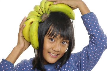 Adorable girl with fresh banana, on the head