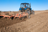 Tractor cultivating soil and preparing a field for planting
