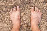 Naked Feet on dry Soil