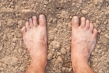 Naked Feet on dry Soil