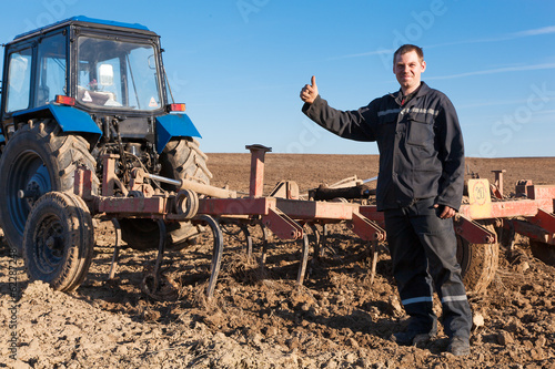 Farmer man standing in cultivated field and showing OK gesture