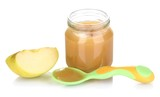 Jar of baby puree with apple and spoon isolated on white