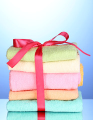 Colorful towels with ribbon on blue background