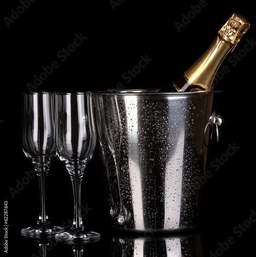 Bottle of champagne in bucket and goblets isolated on black
