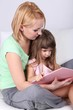 Pretty little girl reading book with mother