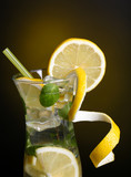 Glass of cocktail with lemon and mint on dark yellow background