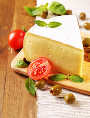 Tasty Camembert cheese with tomatoes, olives and basil,
