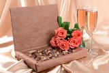 Delicious chocolates in box with flowers on gold background