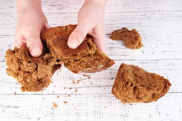 Hands breaking bread on wooden background