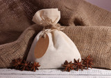 Sack full with spices, on wooden table, on sackcloth background