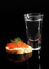 Sandwich with caviar and vodka isolated on black