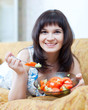 Smiling casual woman eats tomatoes salad