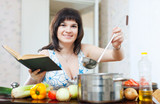 Positive woman cooking with cookery book