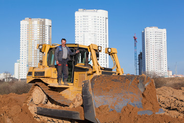Construction worker with bulldozer during earth moving works