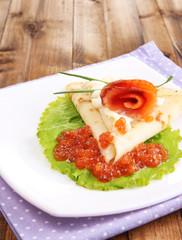 Pancake with salmon, red caviar and mayo, green onion,