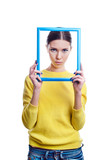 Young beautiful woman holding light blue frame with sad expressi