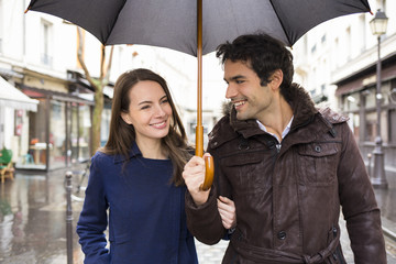 Handsome couple under the rain on street