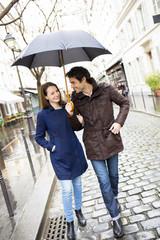 Handsome couple under the rain on street
