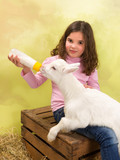 Happy girl feeding baby goat