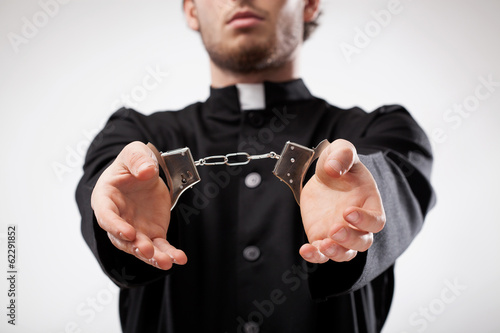 Priest handcuffed
