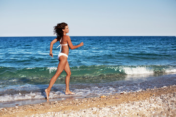Young woman running along the beach.