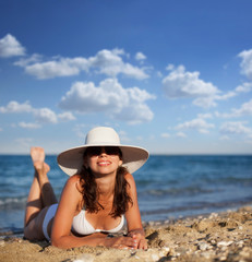 Young woman sunbathes at the seaside.