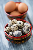 Close-up of raw quail and chicken eggs, vertical shot