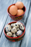 Wooden khokhloma bowls with raw chicken and quail eggs
