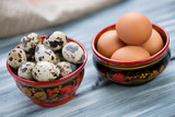 Raw quail and chicken eggs in khokhloma tableware
