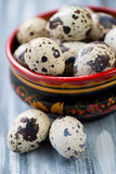 Close-up of raw quail eggs in a wooden khokhloma bowl