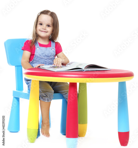 Child sitting at the table and reading a book