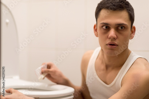 young handsome man sitting in toilet.