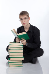 Teenager reading a book on white background