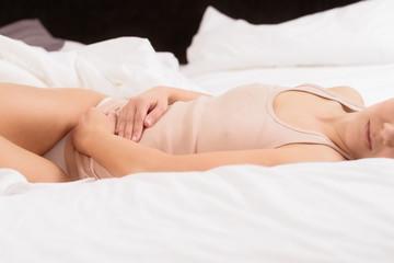 Frau mit Bauchschmerzen im Bett