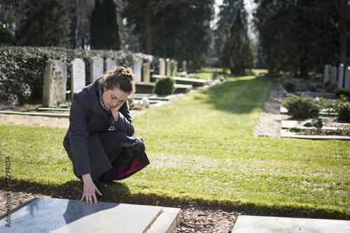 Leinwandbild Motiv widow at grave of deceased husband