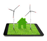 tablet with green house and wind turbines