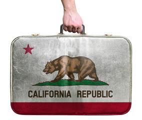 Tourist hand holding vintage leather travel bag with flag of Cal