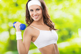 Woman exercising with dumbbell, outdoors