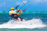 young smiling kitesurfer on sea background